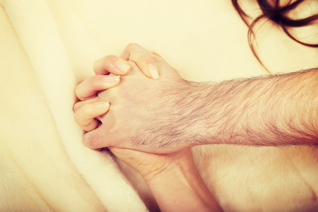 Hands of playful couple lying on bed. Stock Photo