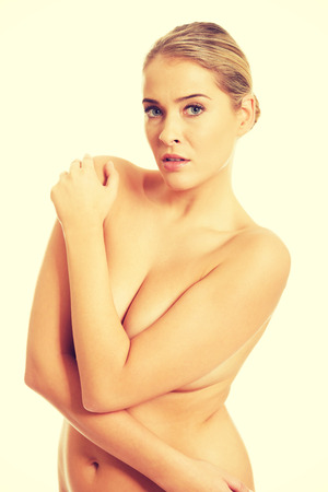 Topless woman looking at camera touching shoulders