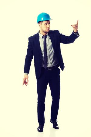 Happy handsome businessman in helmet points his finger up. photo