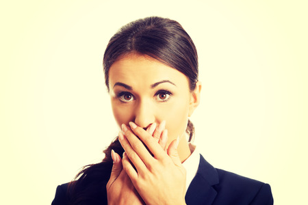 guardar silencio: Retrato de la empresaria que cubre la boca sorprendida.