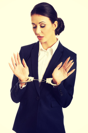 cuffs: Full length businesswoman with handcuffs.