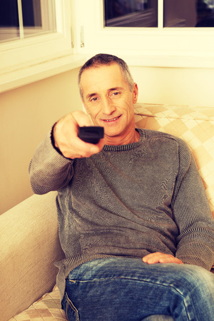 changing channel: Mature man with remote control relaxing in living room