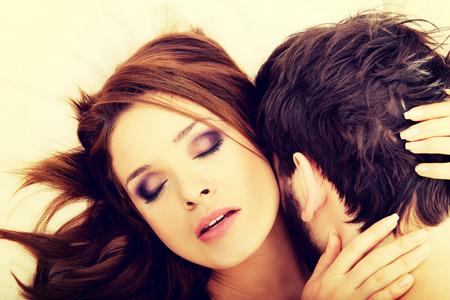 sexo pareja joven: Pareja feliz pareja bes�ndose en la cama.