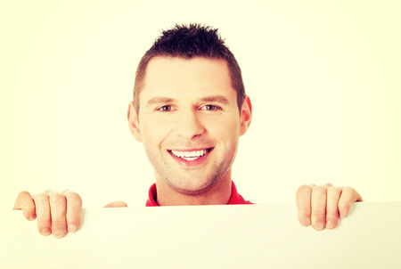 displaying: Happy young man showing and displaying placard with copy space