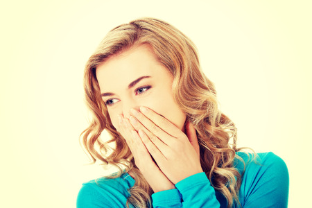 horrify: Woman giggles covering her mouth with hand