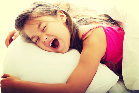 Pretty young girl yawning while waking up photo