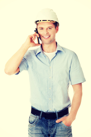 Contractor in hardhat smiles as he talks on his cell phone. photo