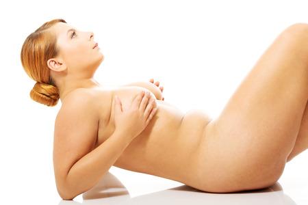 beaux seins: Grande femme nue couch�e sur le sol. Banque d'images