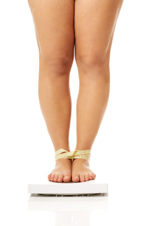 high scale: Overweight woman standing on a scale