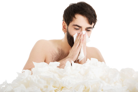 Tissues: Sick man with a lot of tissues sneezing into handkerchief.
