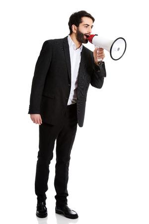 businessman using a megaphone: Handsome businessman shouting using a megaphone.