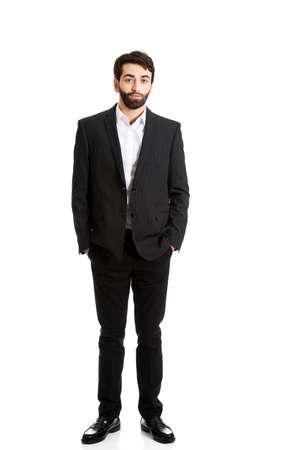 persona de pie: Joven apuesto hombre de negocios sonriente de pie.