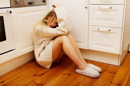 soltería: Triste joven solitaria sentado en la cocina en casa.