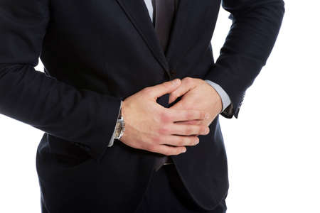 Pain Management: Young handsome businessman suffering from stomach pain. Stock Photo