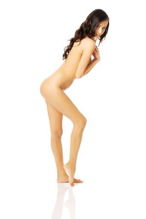 nudo integrale: Vista laterale di una donna nuda con il seno coperto e piegare il ginocchio.