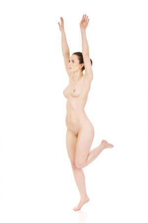 nude woman standing: Beautiful nude woman in drawing pose with her hands up.