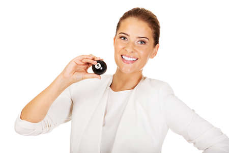 billard: Happy businesswoman holding eight billiard ball. Winning concept.