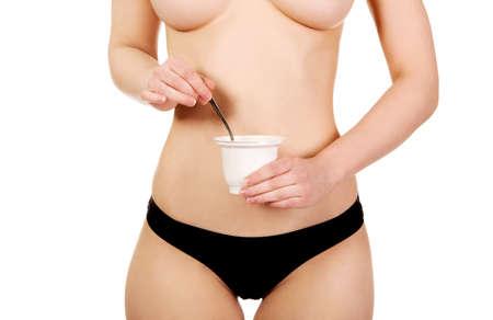 Schöne Frau in der Unterwäsche, die Joghurt isst. Standard-Bild