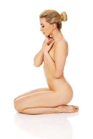 donna completamente nuda: Giovane donna nuda seduta sul pavimento e toccare il viso