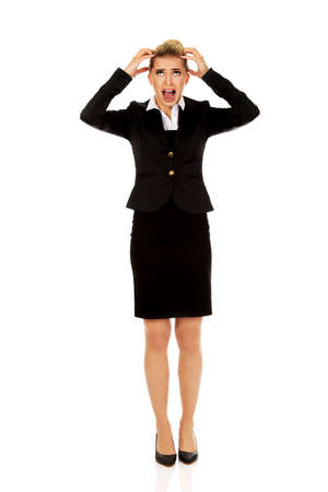 angry person: Angry businesswoman pulling her hair and screaming. Stock Photo