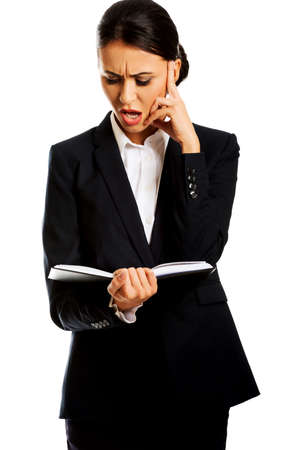 Irritated businesswoman reading her notes.