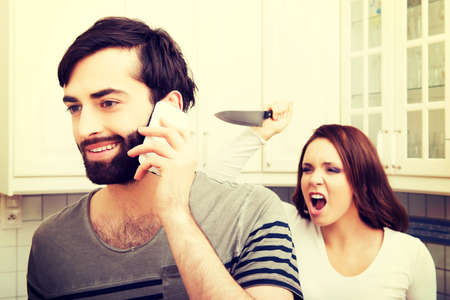 pan: Young rage woman hitting her talking partner with frying pan. Stock Photo