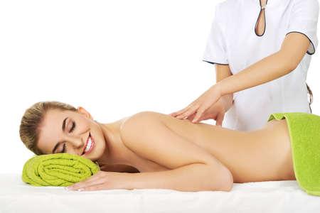masajes relajacion: Sonrisa hermosa mujer joven acostado en una mesa de masaje y tiene masaje. Foto de archivo
