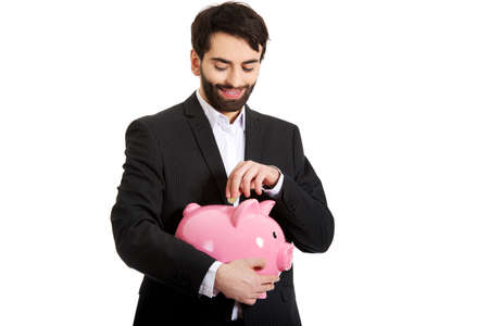 coin bank: Happy handsome businessman putting a coin to piggybank.