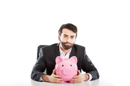 piggybank: Young businessman with piggybank by a desk.