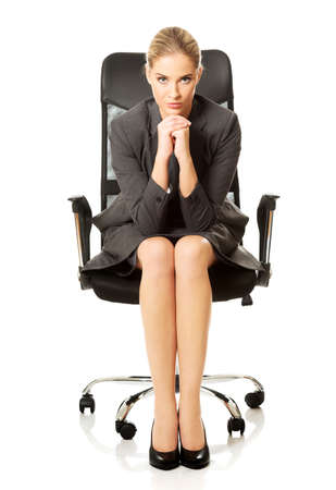 chin on hands: Sitting businesswoman with hands on chin. Stock Photo