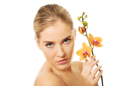 topless: Topless woman with an orange orchid flower. Banque d'images