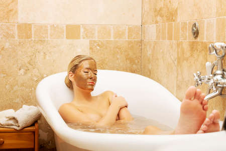 chocolate mask: Woman relaxing in a bath with chocolate mask on her face.