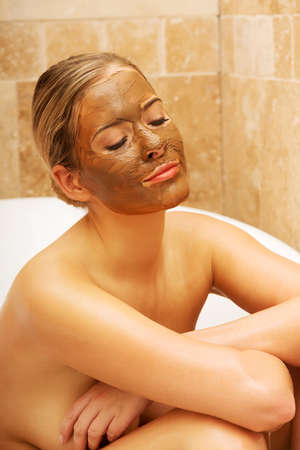 chocolate mask: Spa woman sitting in a bath with chocolate mask on face. Stock Photo