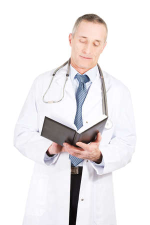 proffesional occupation: Experienced mature male doctor reading his notes.