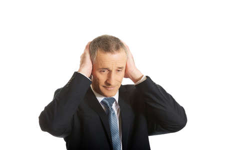 hands covering ears: Portrait of tired businessman covering ears with hands.