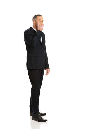 covering mouth: Full length businessman covering mouth. Stock Photo
