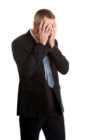 hands covering face: Stressed businessman covering his face with hands. Stock Photo