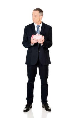 full length: Full length confused businessman holding piggybank.