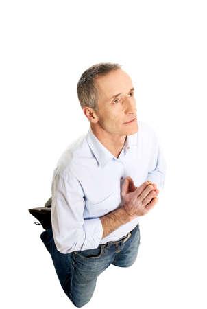 man kneeling: Mature man kneeling and praying to God. Stock Photo