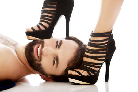possessive: Sexy womans foot in high heel on mans face, dominating him. Stock Photo