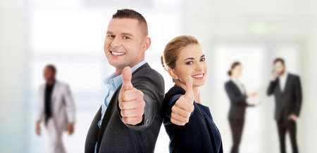 businessman smiling: Happy business couple showing thumbs up.