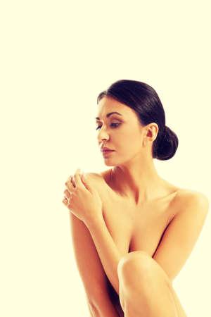 seins nus: Femme aux seins nus couvrant sa poitrine et regardant vers le bas. Banque d'images