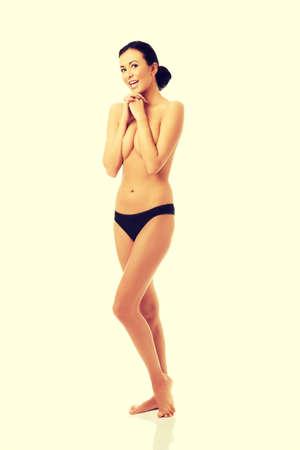 seins nus: Femme aux seins nus en culotte couvrant sa poitrine.