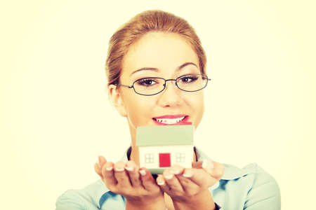 selling service smile: Happy businesswoman presenting a house model.