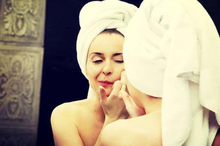 espejo: Mujer hermosa que exprimen su acn� frente al espejo.