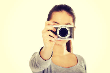 camera: Teen woman taking a photo with a camera.