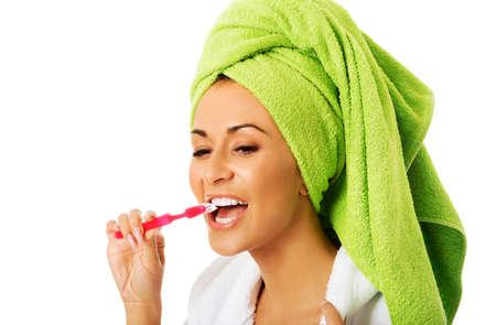 beautiful teeth: Spa woman in bathrobe brushing teeth.