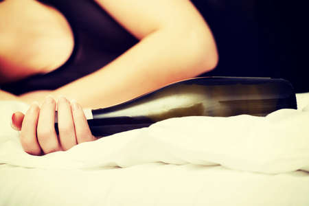 stressed woman: Drunk woman sleeping on bed with bottle of wine.