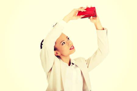 empty wallet: Unhappy african businesswoman shaking empty wallet.
