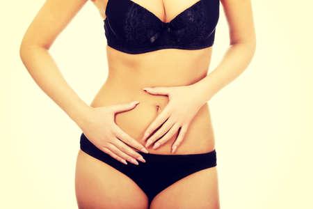 ropa interior: Mujer en ropa interior tocando su vientre delgado.